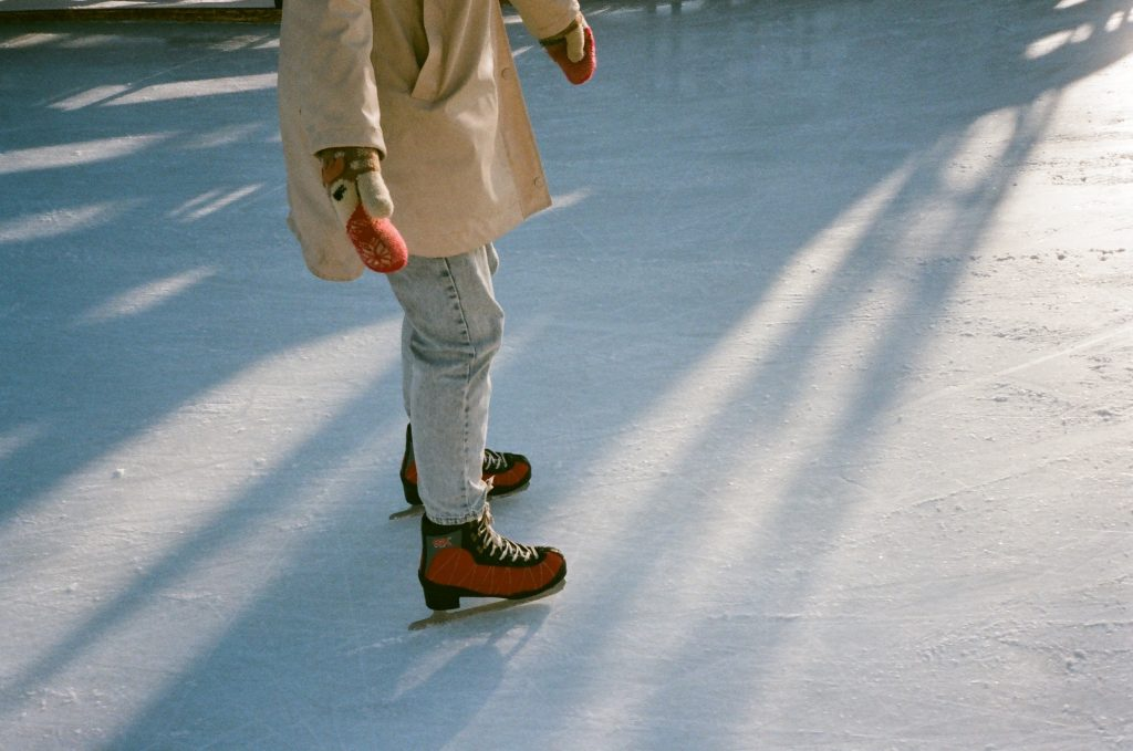 person skating on ice rink with mitts