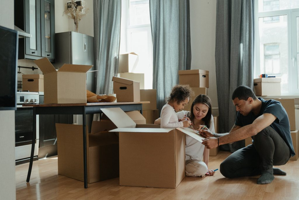 family in living room with moving boxes